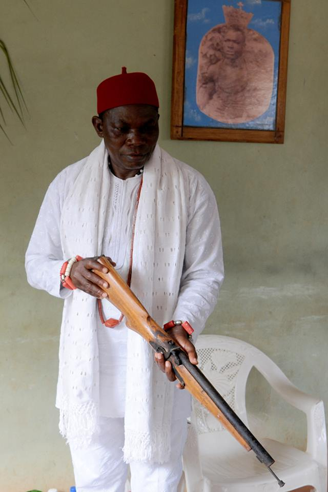 With a photo of his Grandfather Obi (King) Okobi 1, as a backdrop, HRM shows off an Adaka (ancient hand canon) part of the Royal collection.